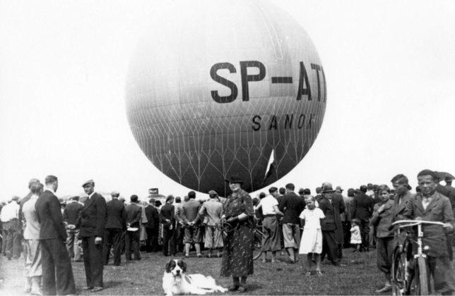 """Pierwszy lot balonu """"Sanok Autor: Leon Gottdank Czas wykonania: 21.06.1936 r. Fotografia przedstawia balon """"Sanok"""" na sanockich błoniach nad Sanem. Wokół balonu zgromadzeni widzo-wie. Na balonie widoczne napisy: SP – ATN/ SANOK."""