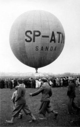 """Pierwszy lot balonu """"Sanok"""" Autor: Leon Gottdank Czas wykonania: 21.06.1936 r. Fotografia przedstawia balon """"Sanok"""" na sanockich błoniach nad Sanem. Wokół balonu zgromadzeni widzowie. Na balonie widoczne napisy: SP – ATN/ SANOK."""
