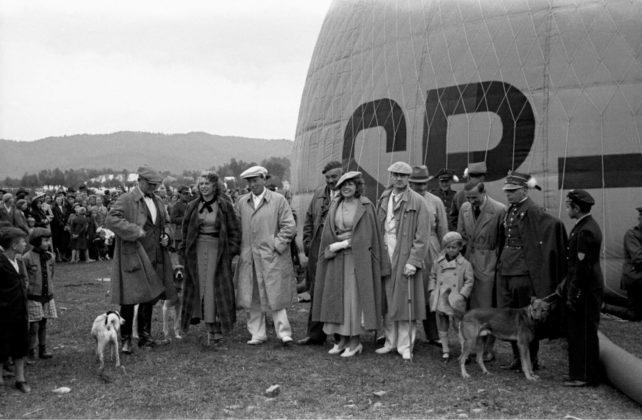 """Pierwszy lot balonu """"Sanok"""" Autor: Stanisław Potocki, 21.06.1936 r. Fotografia przedstawia balon """"Sanok"""" na sanockich błoniach nad Sanem utrwalony w trakcie napełniania. Wokół balonu zgromadzeni widzowie. Przed balonem grupa osób. Trzeci z lewej (w jasnym kaszkiecie) Oskar Schmidt – założyciel i dyrektor Fabryki Gumy oraz prezes sanockiego Klubu Balonowego. Obok, prawdopodobnie, jego żona."""